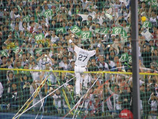 外野フェンスに登りファンの声援に応える古田